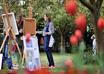 Two women chatting near artist's easels set up in a public green space