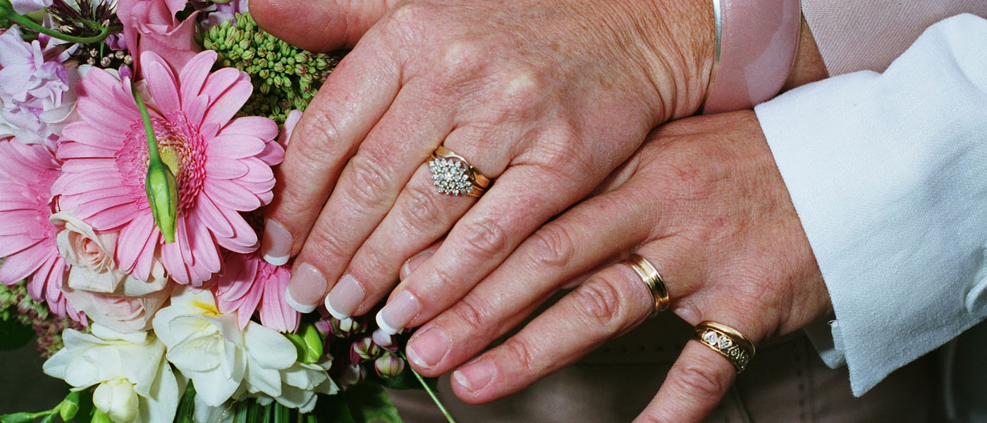 Close-up photograph of two hands with engagement and wedding rings