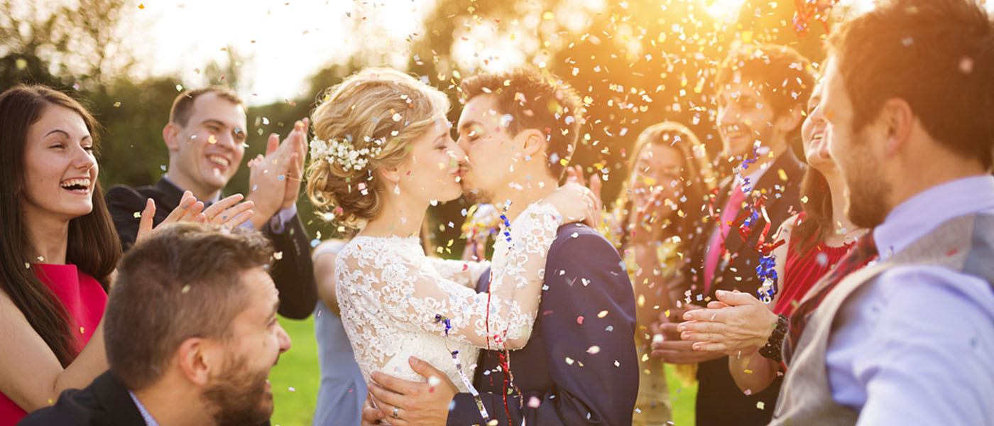 Bride and groom kissing while friends and family throw confetti